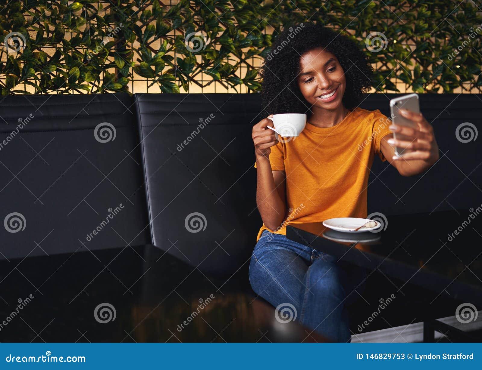采取在手机的微笑的年轻女人selfie