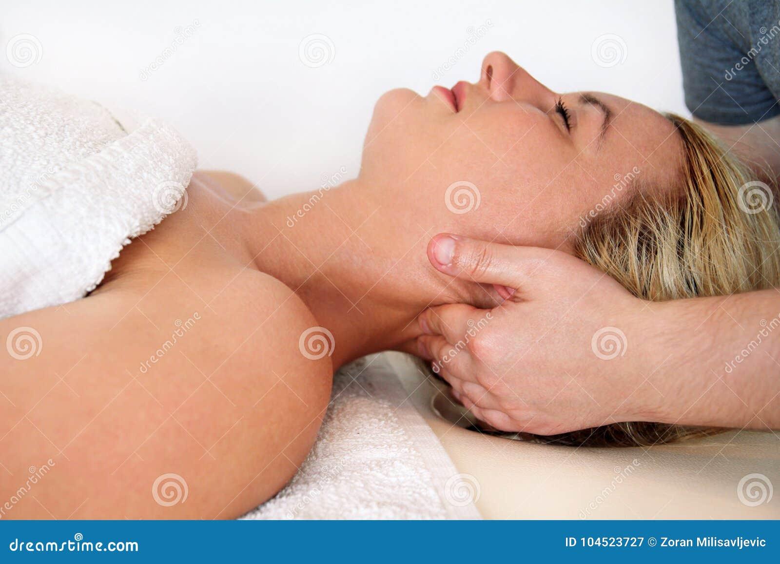 采取按摩脖子的妇女干涉在按摩桌上