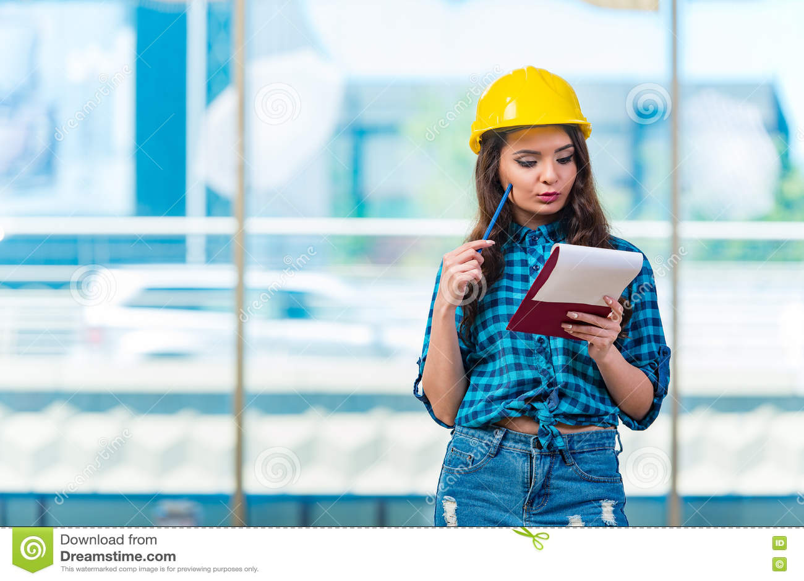 采取笔记的妇女建造者在建造场所