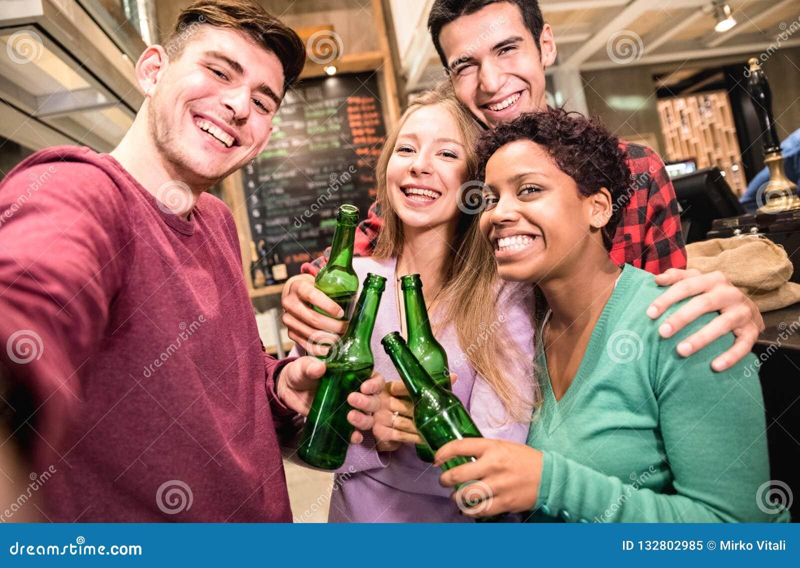 采取selfie和喝啤酒的多种族朋友在花梢啤酒厂客栈