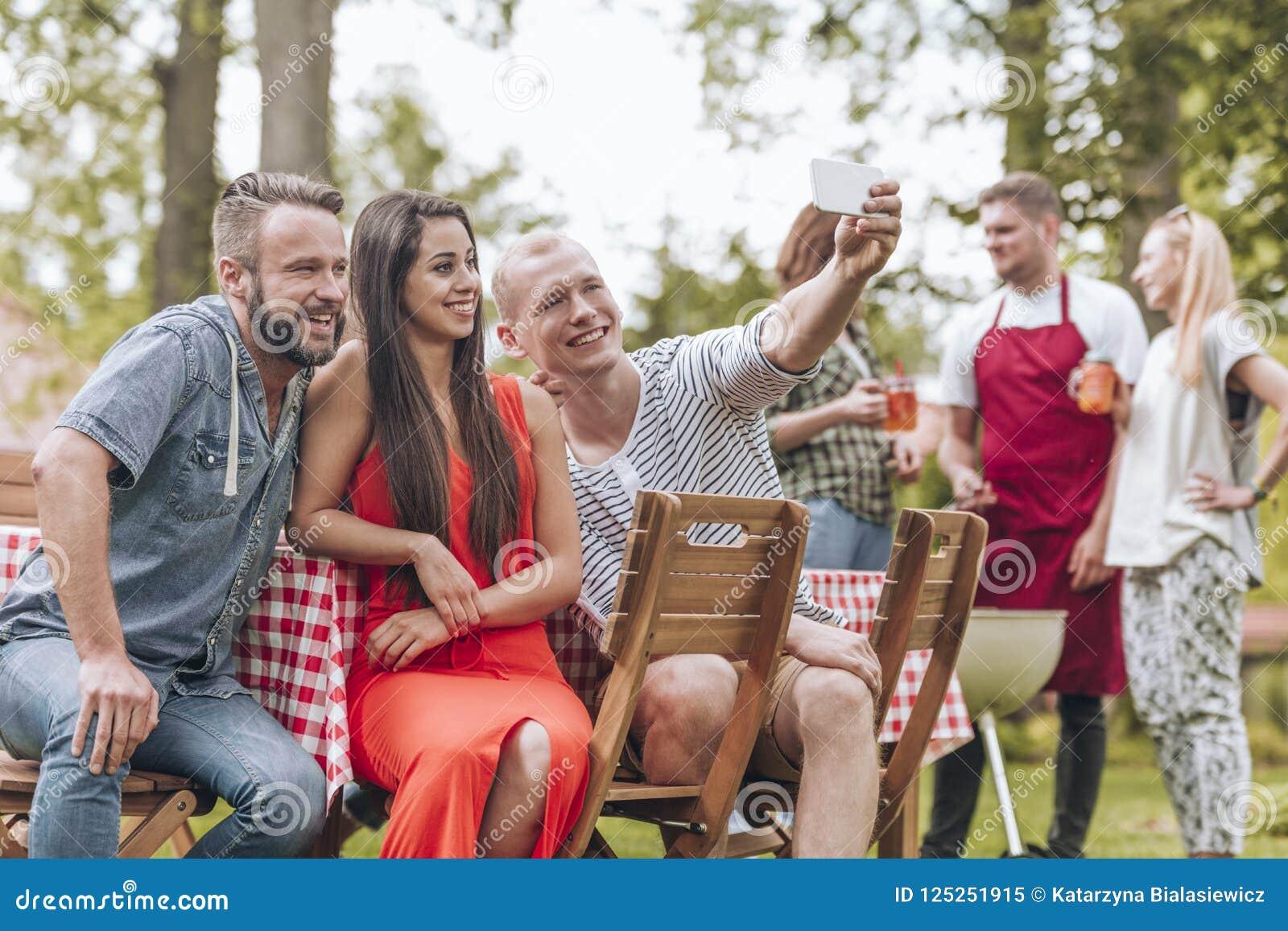 采取selfie的三个朋友在夏天格栅党outsid期间