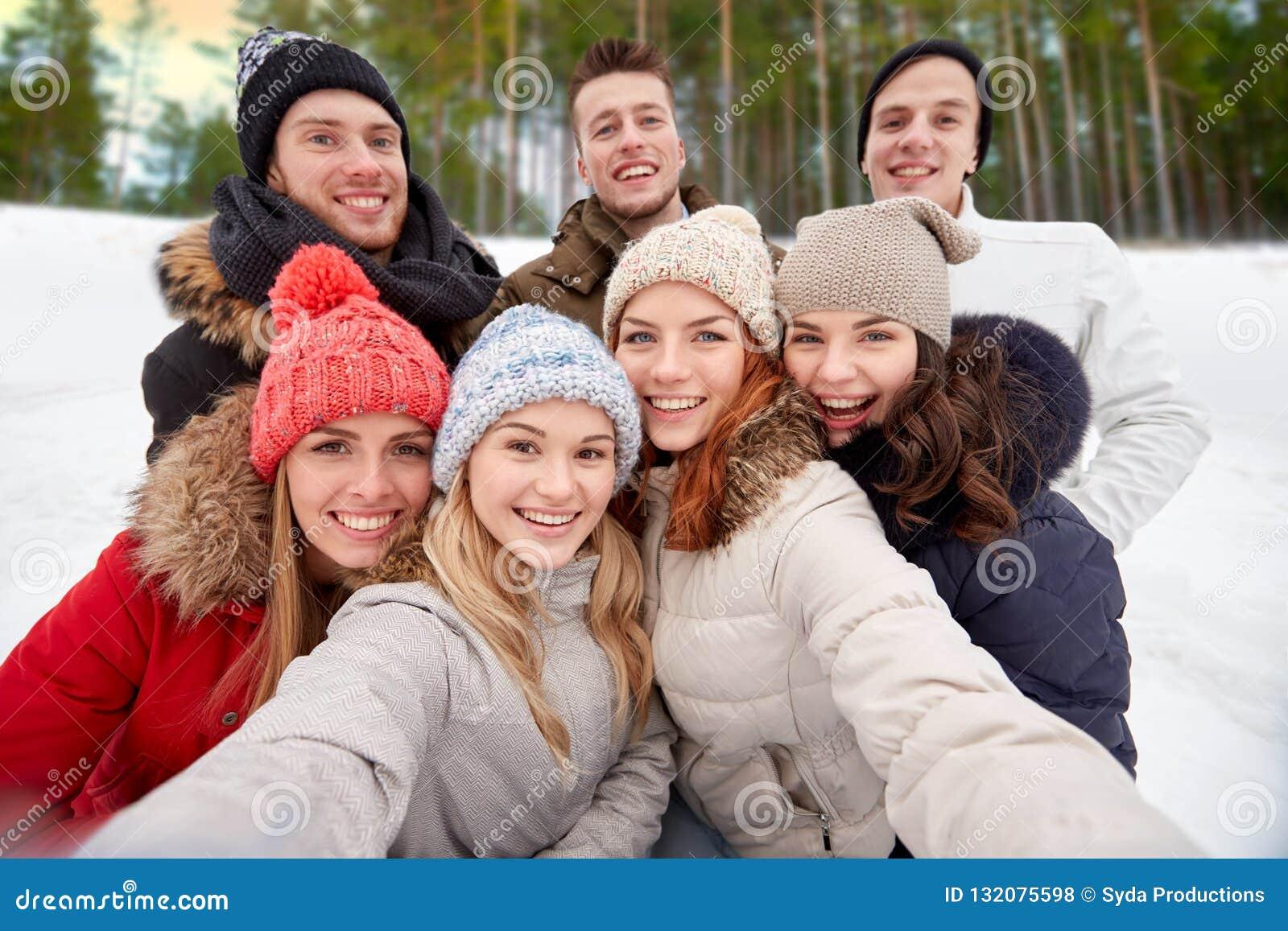 采取selfie的小组朋友户外在冬天