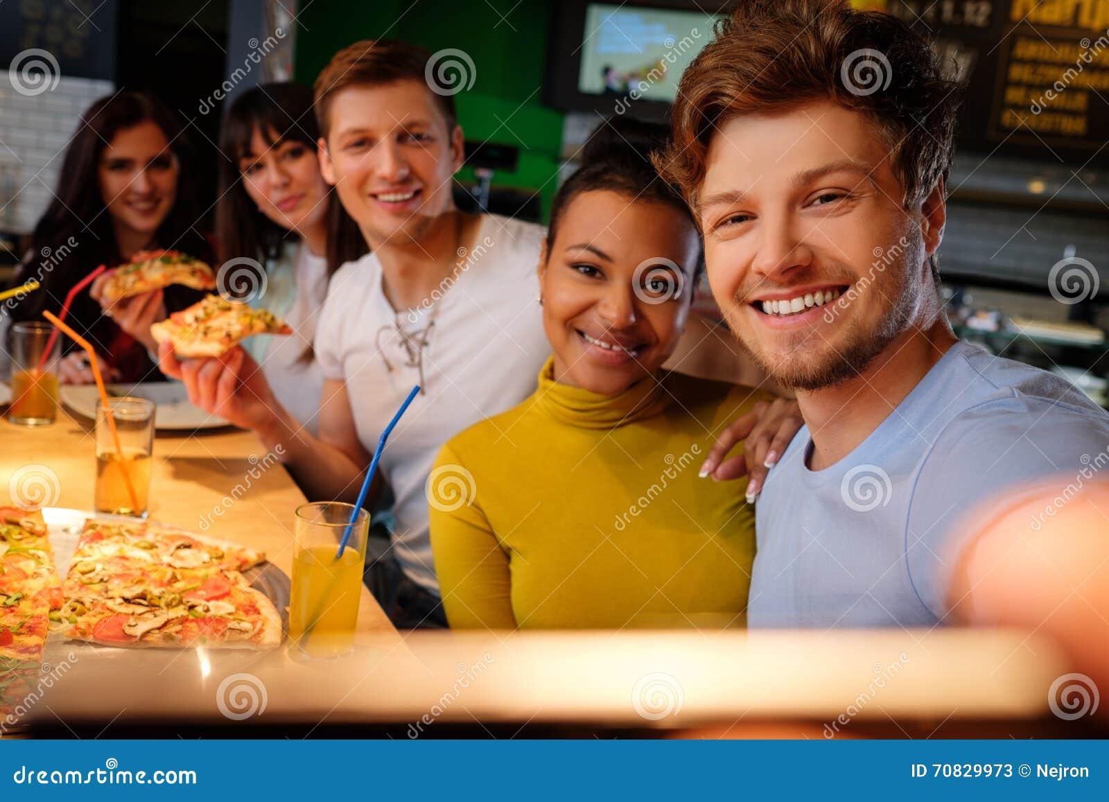 采取selfie的快乐的多种族朋友在比萨店
