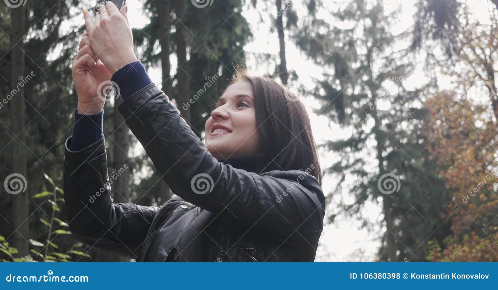 采取Selfie的美丽的年轻深色的妇女使用智能手机 关闭使用智能手机的愉快的女孩户外
