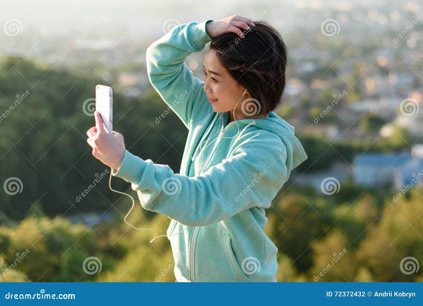 采取selfie的肉欲的年轻日本妇女室外在公园使用她电话和微笑
