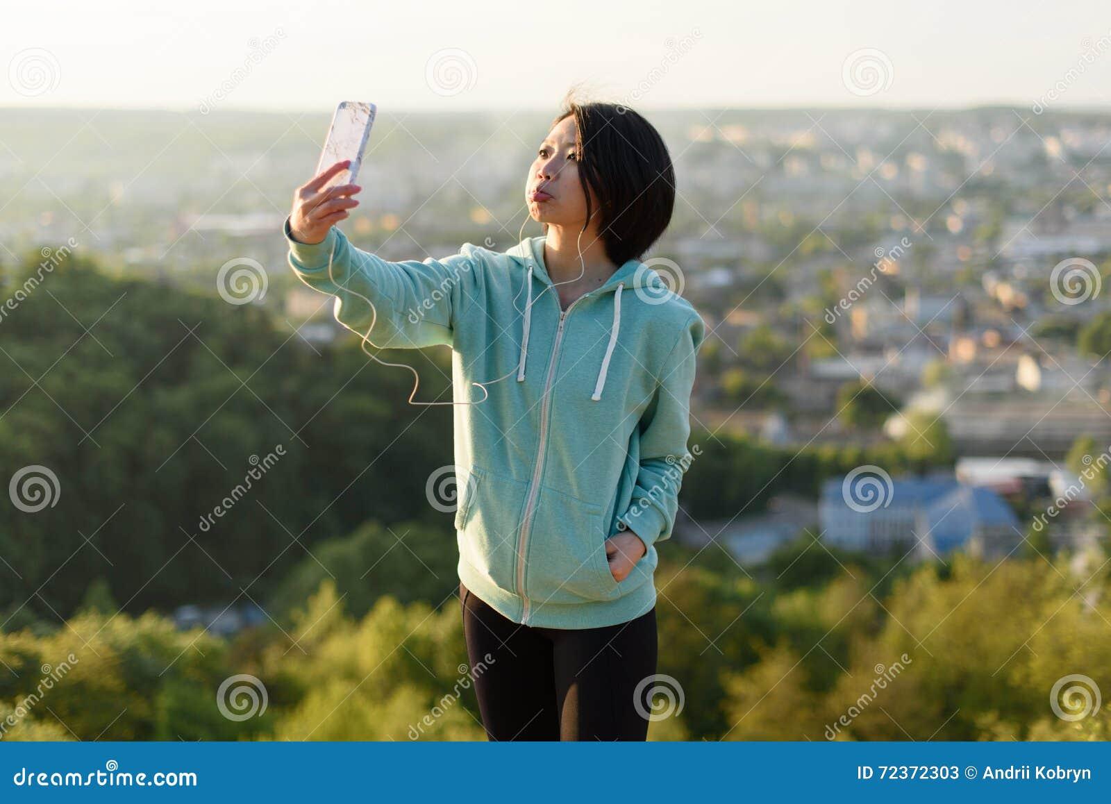 采取selfie的运动服的可爱的年轻日本妇女室外在绿色夏天公园公园使用她的电话和