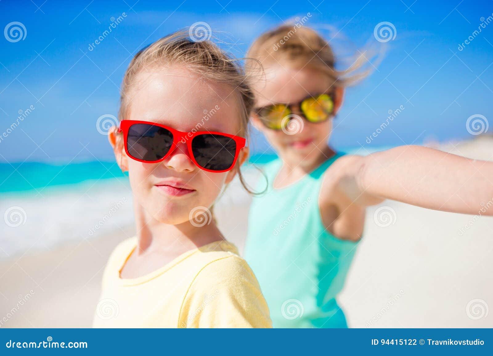 采取selfie的逗人喜爱的小女孩在异乎寻常的海岛上的热带海滩在暑假时