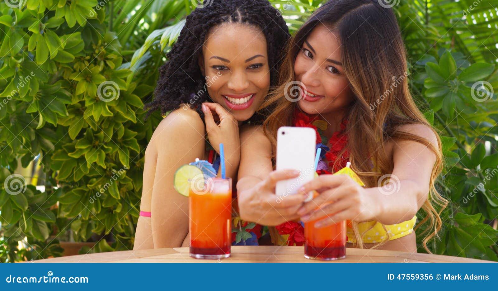 采取与手机的黑人和亚裔妇女中景selfie,当热带假期时.