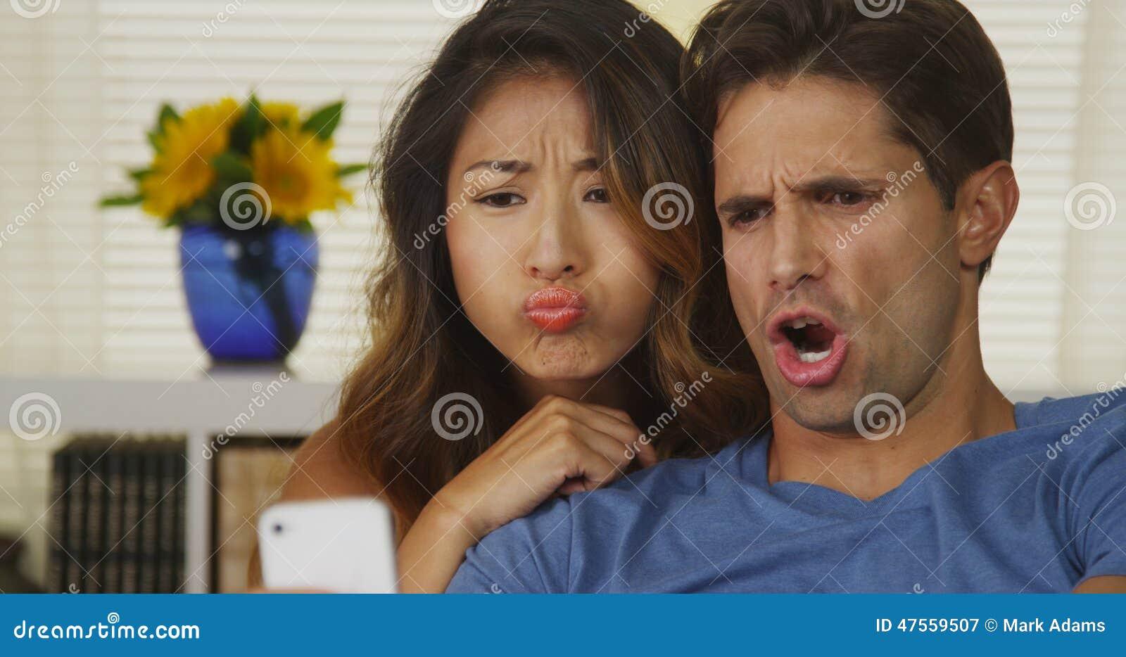 采取selfies的混合的族种夫妇