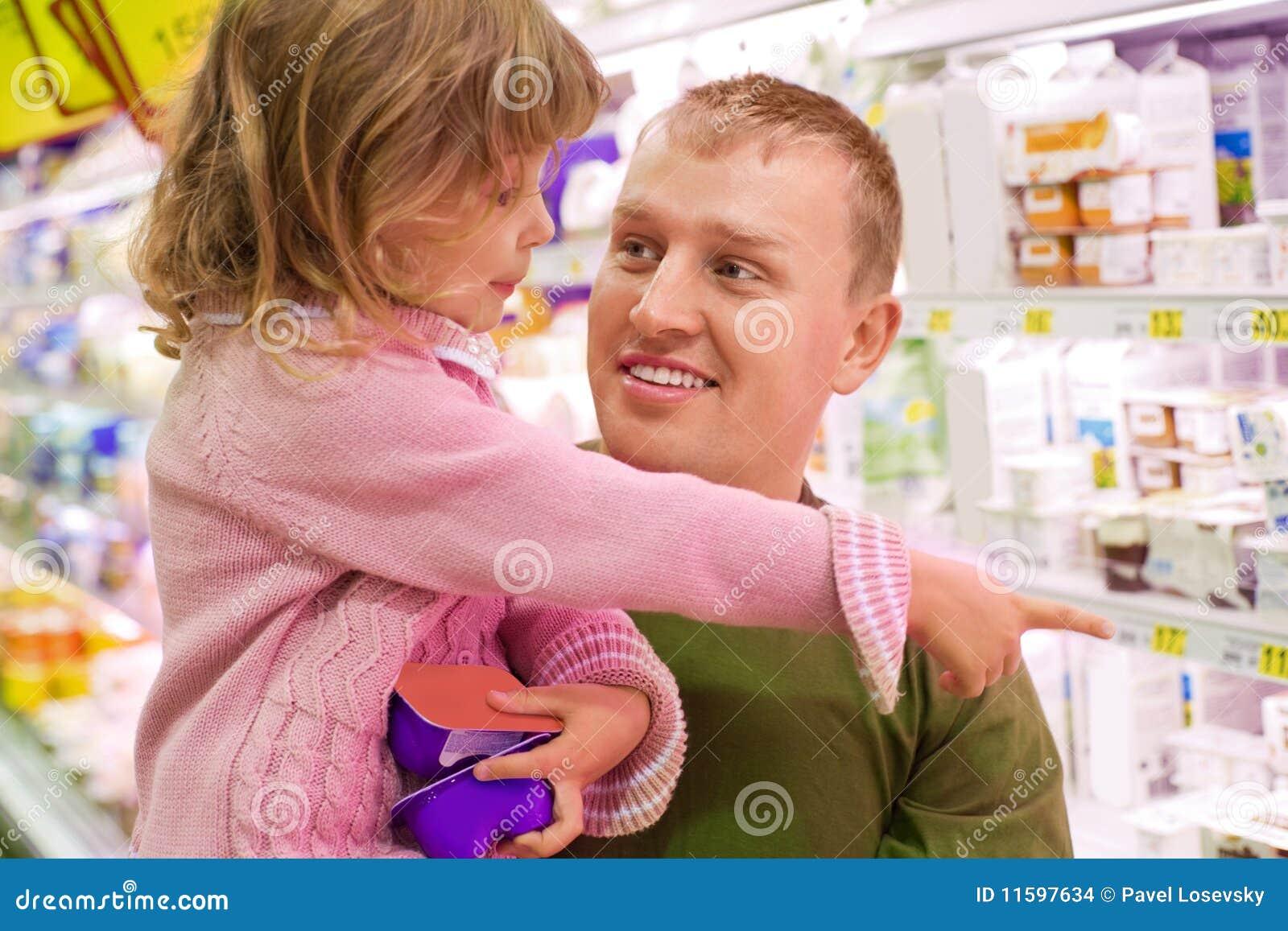 采购女孩人微笑的超级市场酸奶
