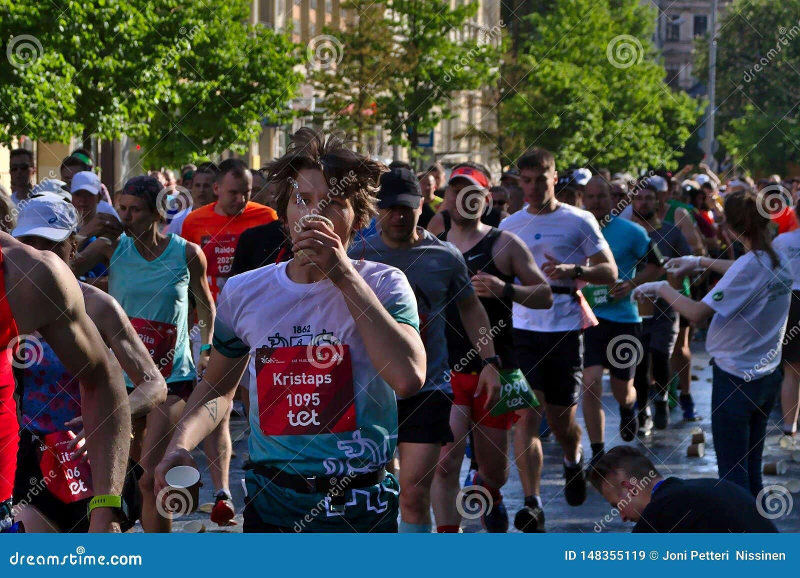 里加,拉脱维亚- 2019年5月19日:马拉松运动员年轻人饮用水