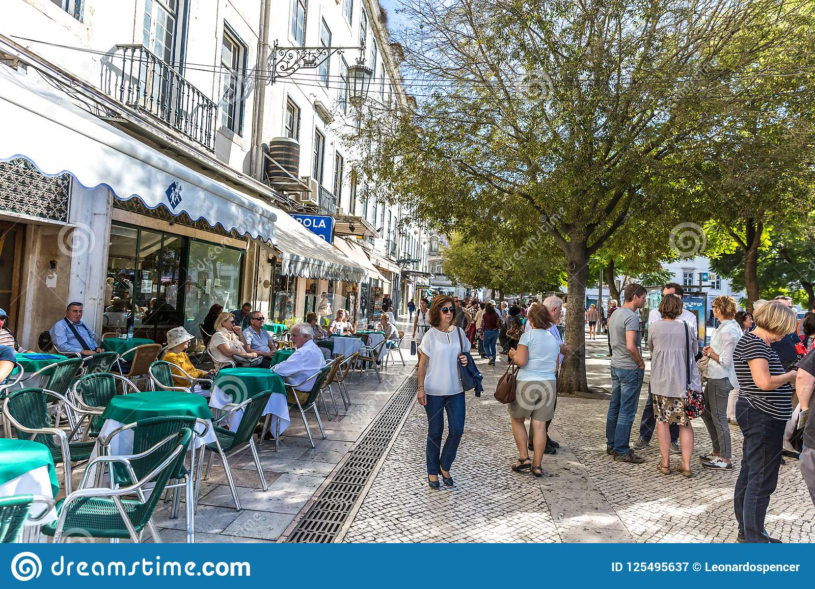 里斯本、葡萄牙- 2018年5月9日-走在一条传统路的游人和本机在街市里斯本,餐馆和树我
