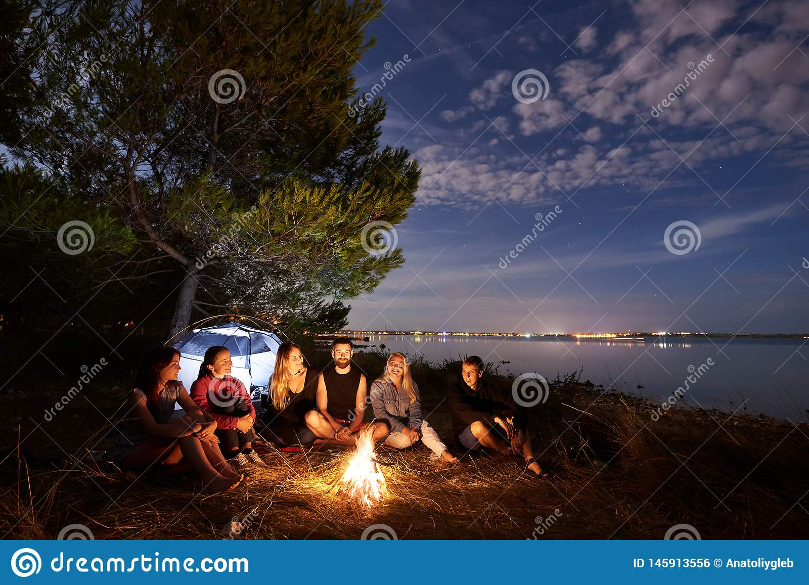 野营在岸的夜夏天 小组在营火附近的年轻游人在平衡天空下的帐篷附近