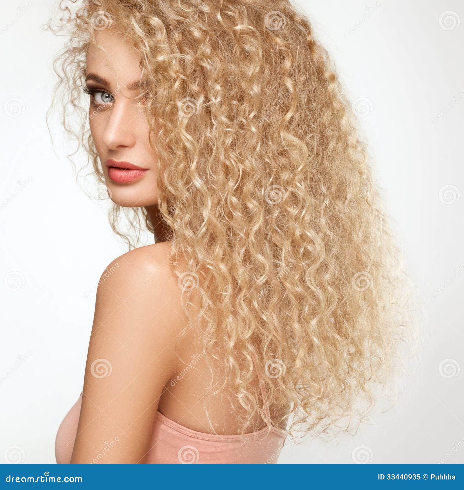 金发。有卷曲长的头发的美丽的妇女。