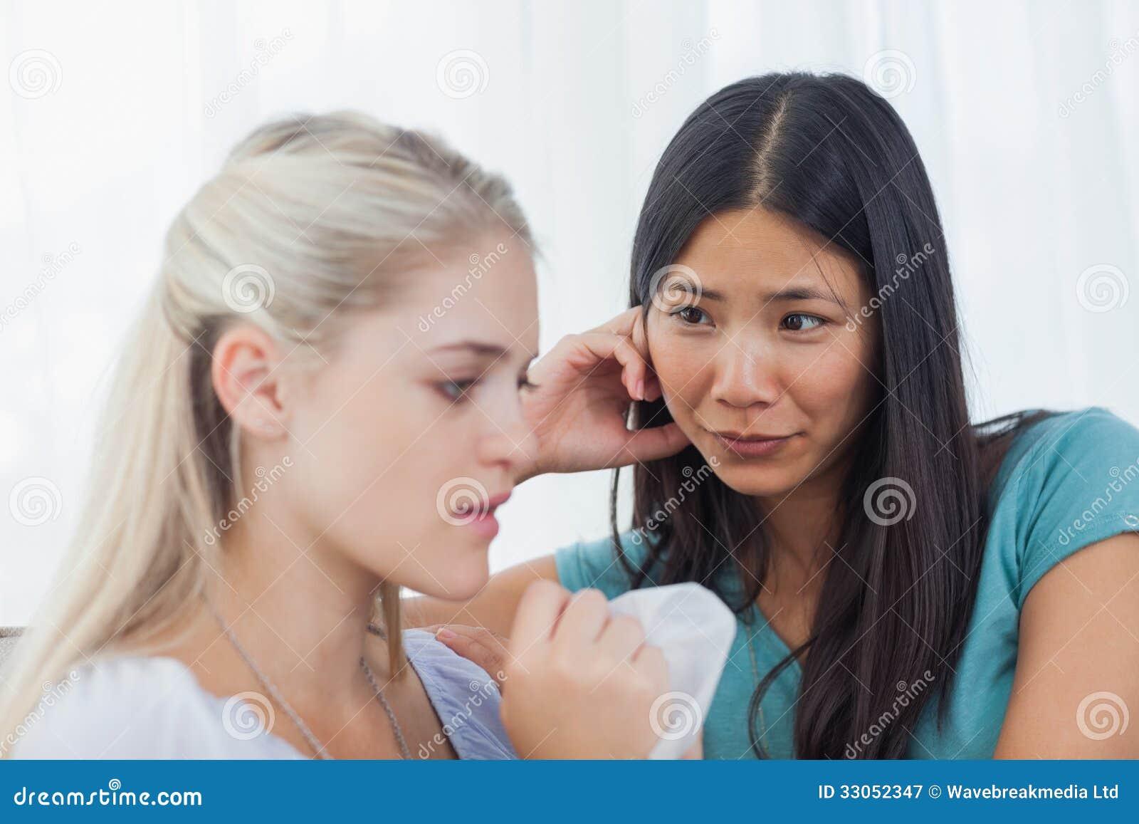金发碧眼的女人哭泣和谈话作为她的朋友听着