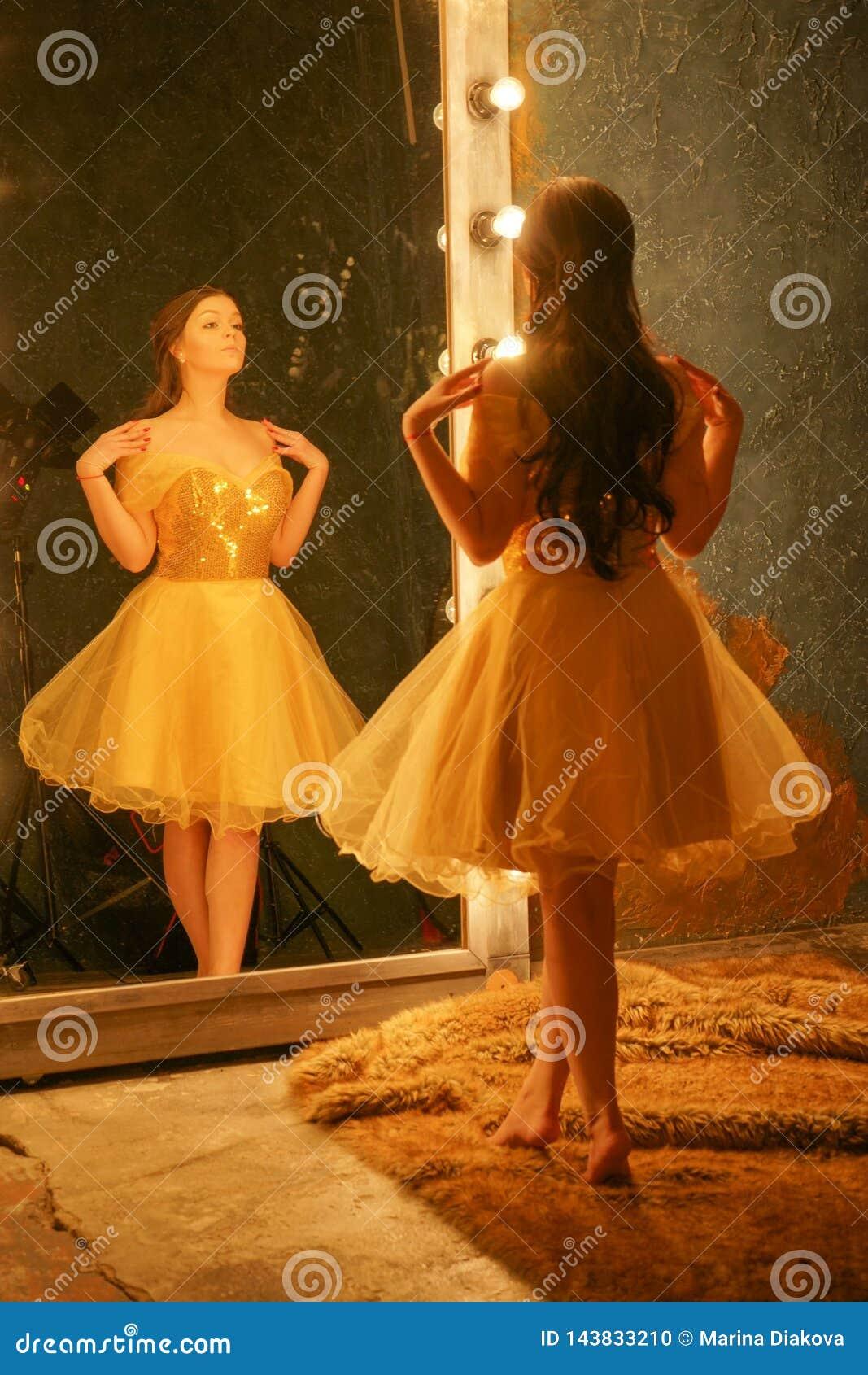 金子晚礼服的美丽的少女在毛皮地毯站立在一个框架的一个大镜子附近与光和神色入她的ref