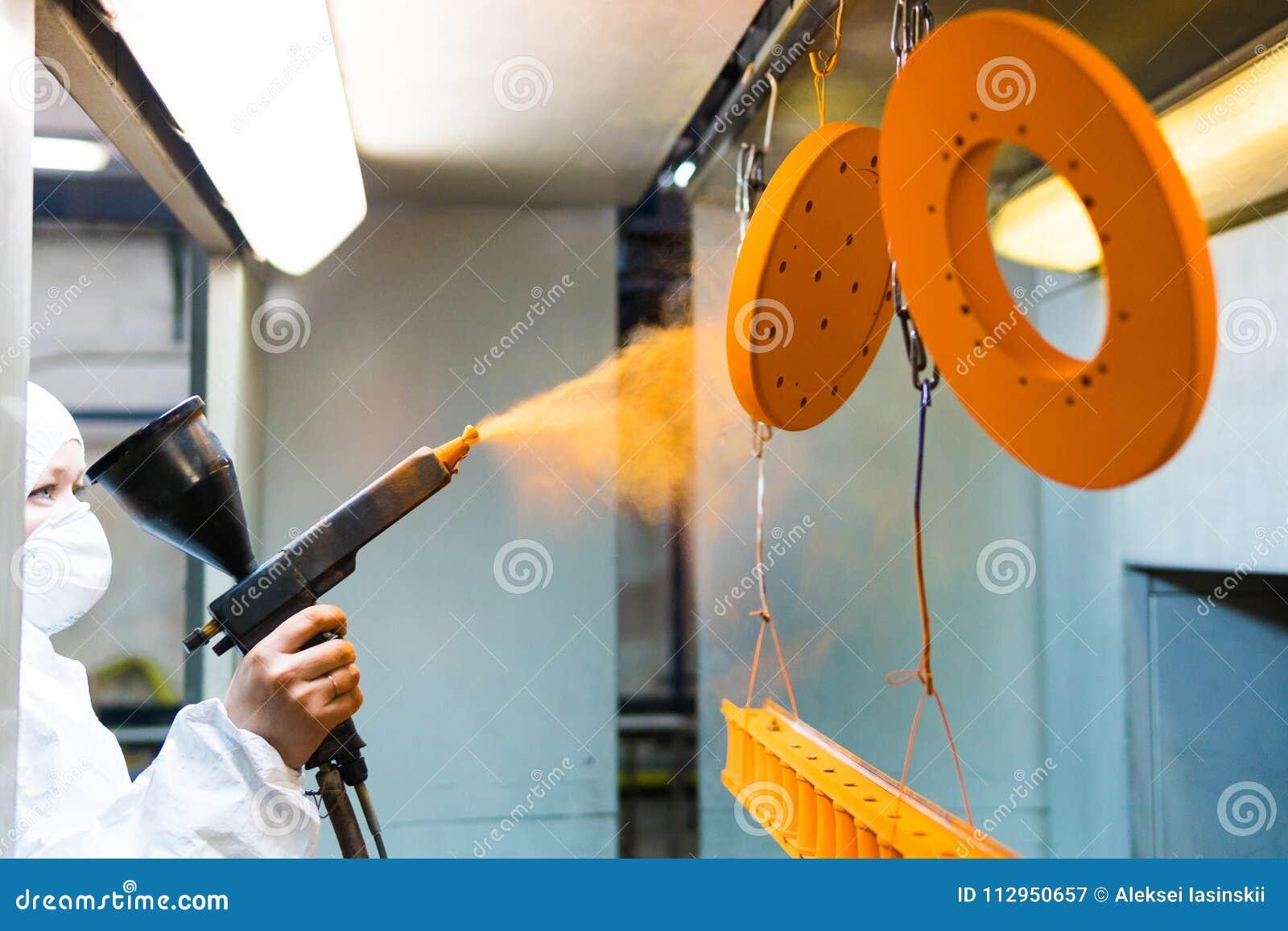 金属零件粉末涂层  防护套服的一名妇女喷洒从一杆枪的粉末油漆在金属制品