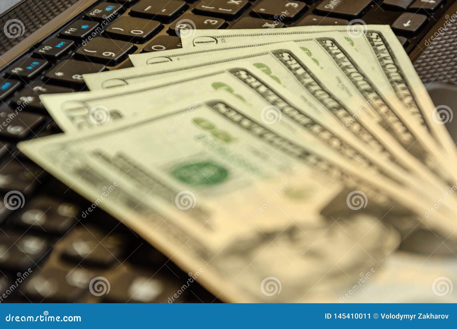 金钱在膝上型计算机键盘的现金钞票 E