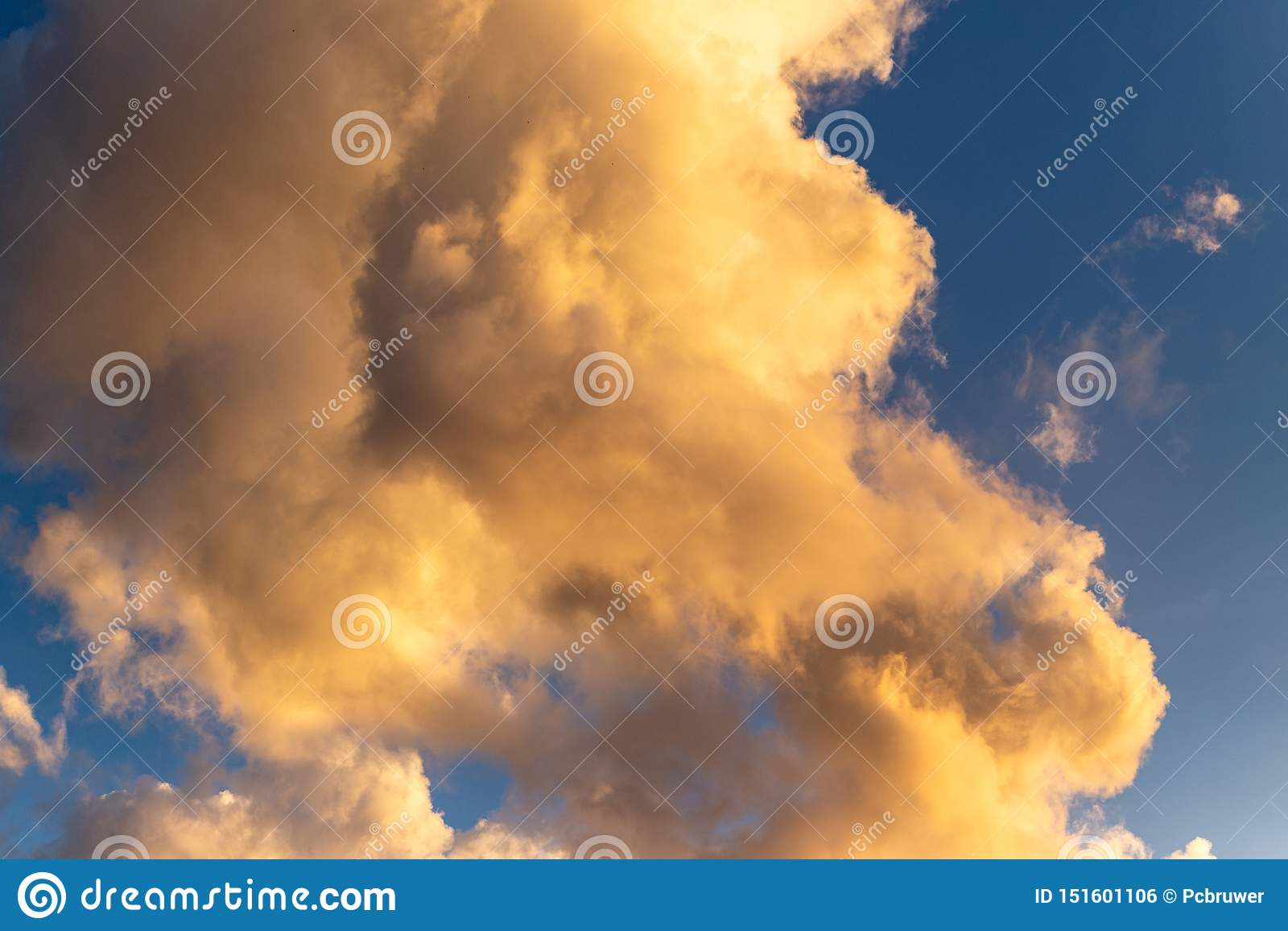 金黄小时云彩有深刻的蓝色背景