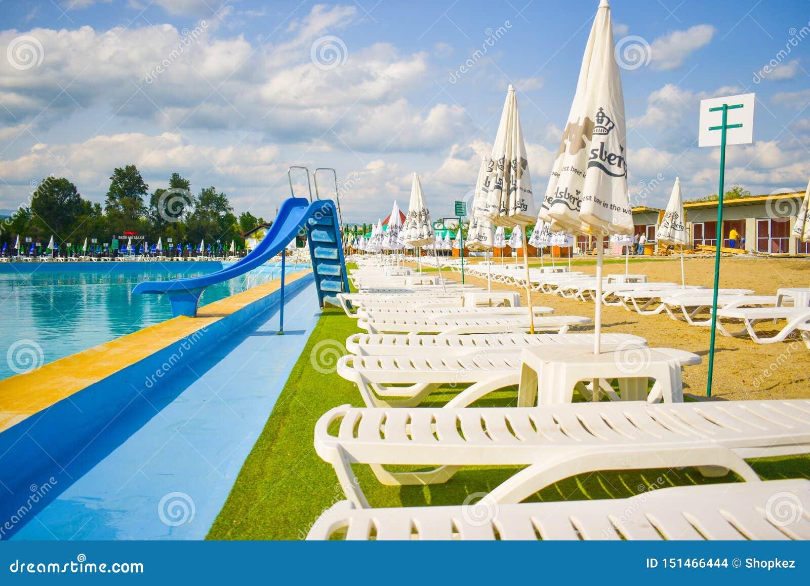 金黄沙子和白色海滩睡椅与伞在大游泳场附近子线的Ostroveni从Ramnicu瓦尔恰 罗马尼亚-