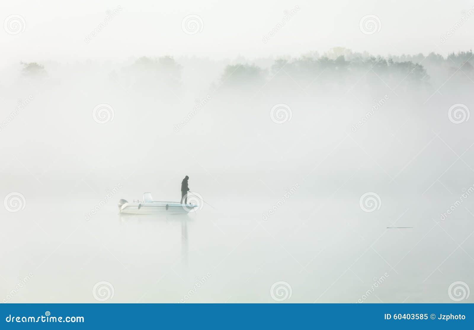 钓鱼在一场厚实的早晨雾