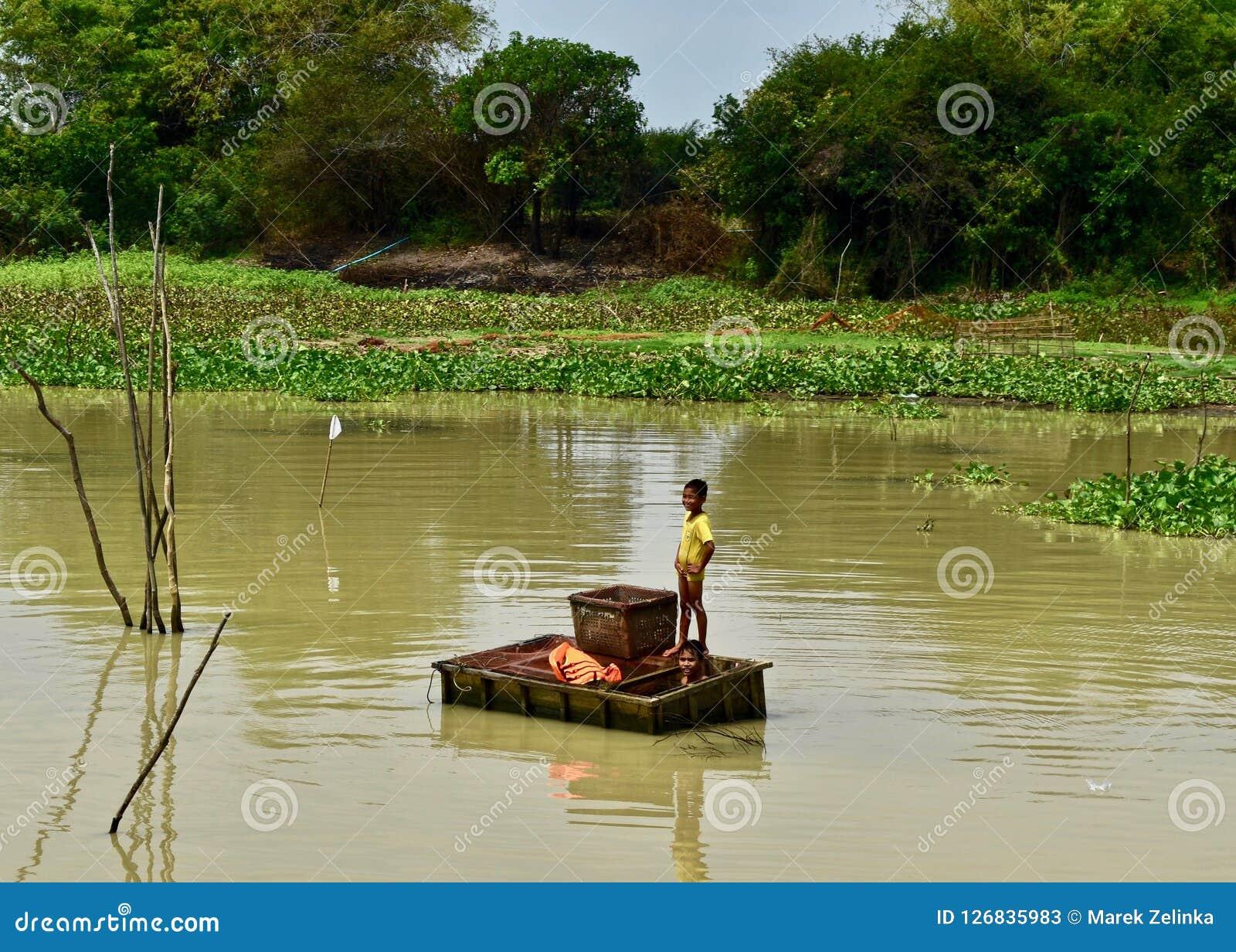 钓鱼在一条河的孩子在柬埔寨