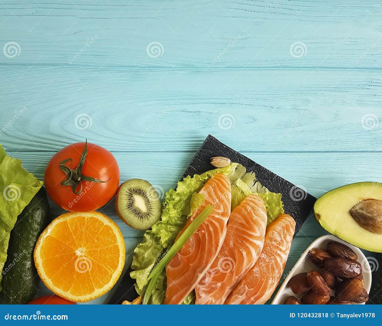 钓鱼在不同蓝色木的背景的三文鱼吃晚餐健康产品