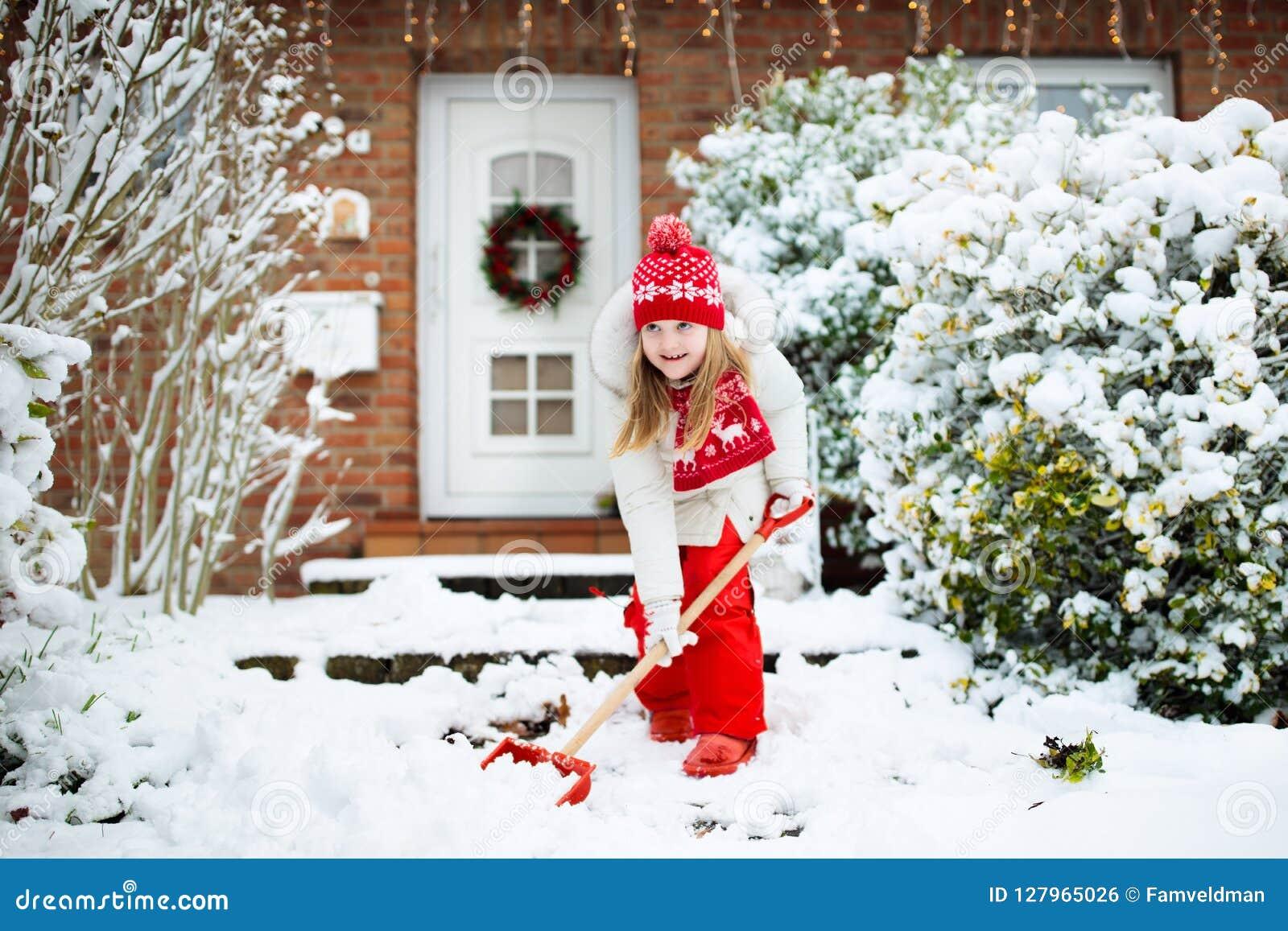 铲起冬天雪的孩子 孩子清除车道