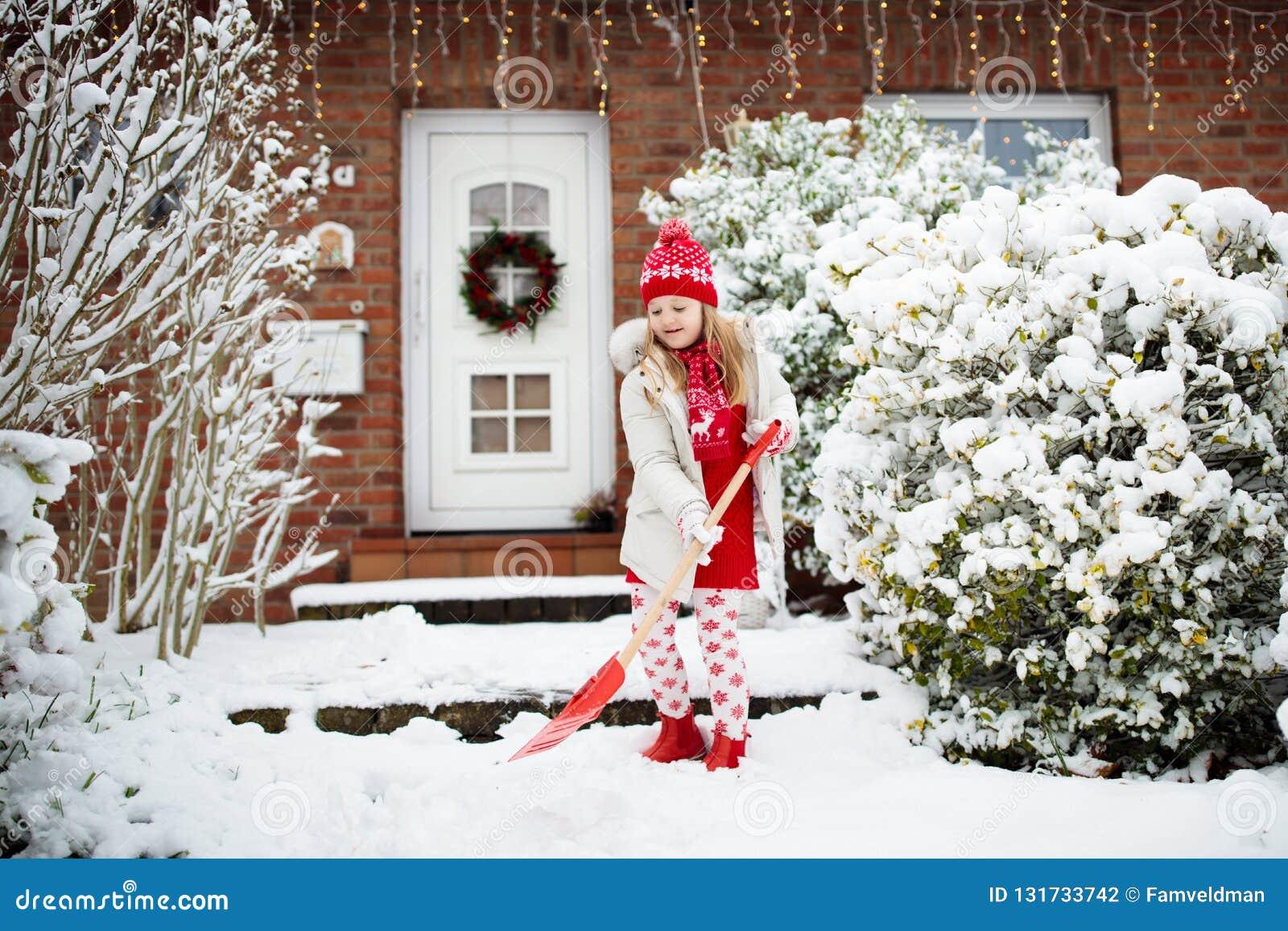 铲起雪的孩子 有锹清洁车道的小女孩在冬天暴风雪以后 以后安置门的孩子清楚的道路