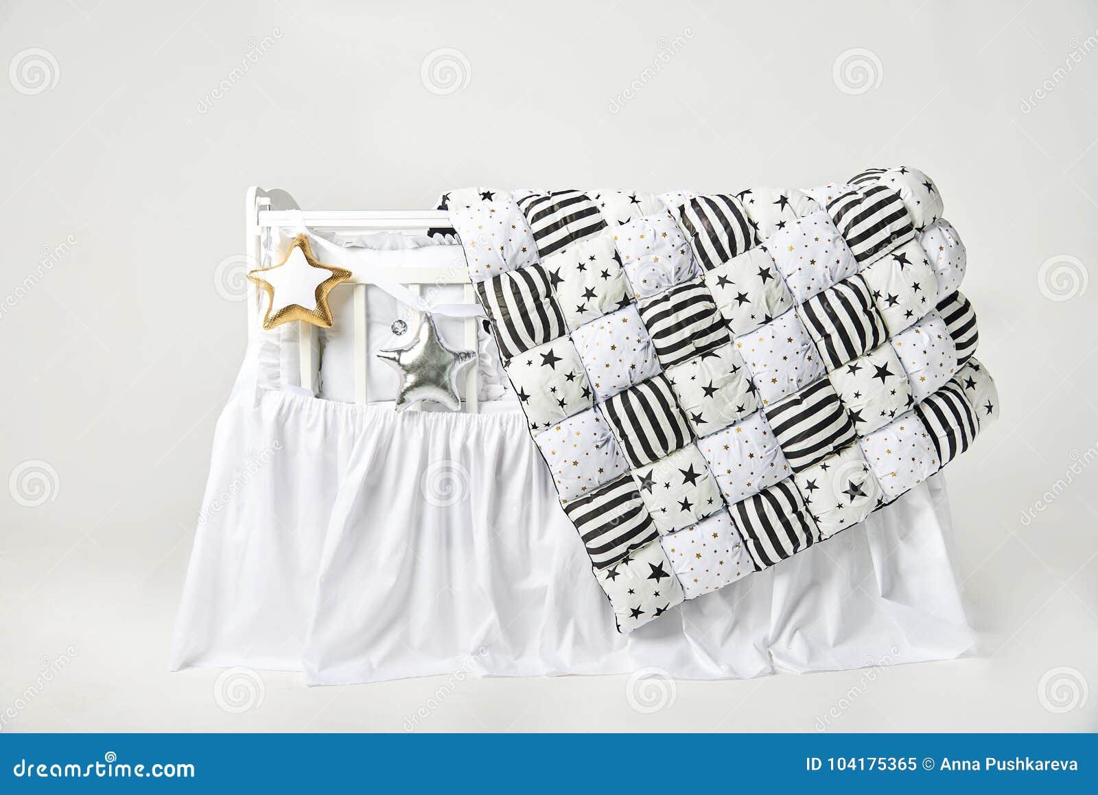 银和金星状枕头和补缀品橡皮奶嘴在一张白色婴儿床