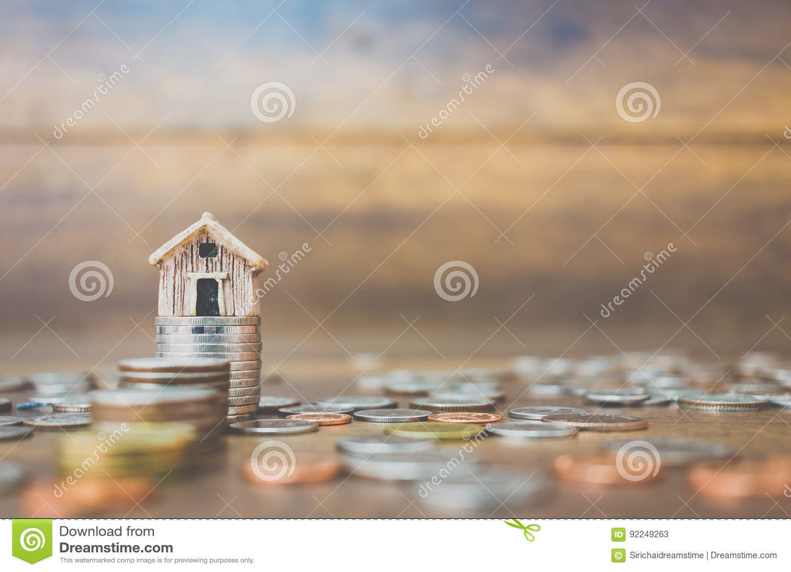 铸造在木背景的金钱和房子模型