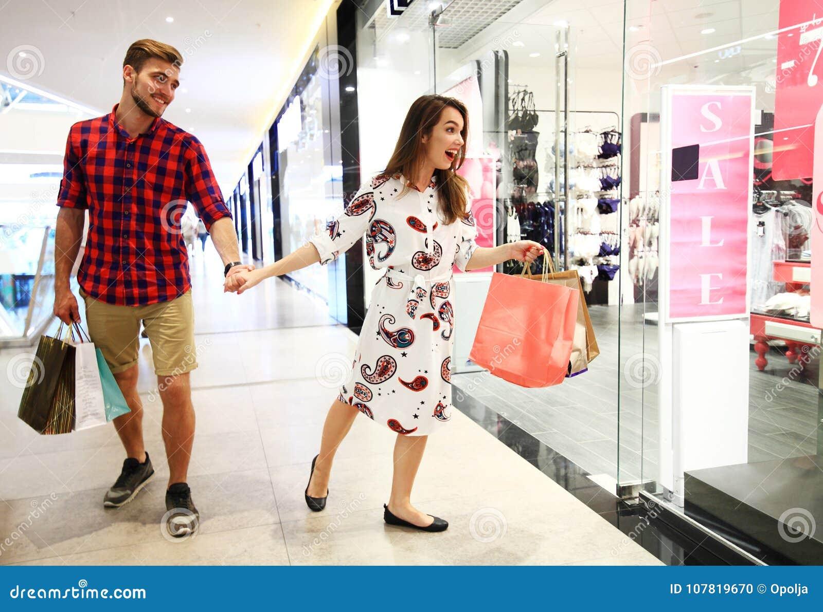 销售、消费者至上主义和人概念-愉快的年轻加上走在购物中心的购物袋