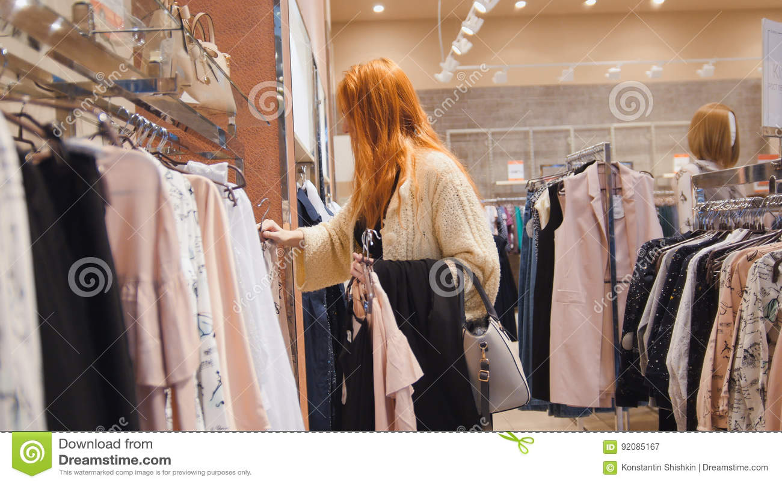 销售-妇女在礼服商店选择衣裳-购物概念