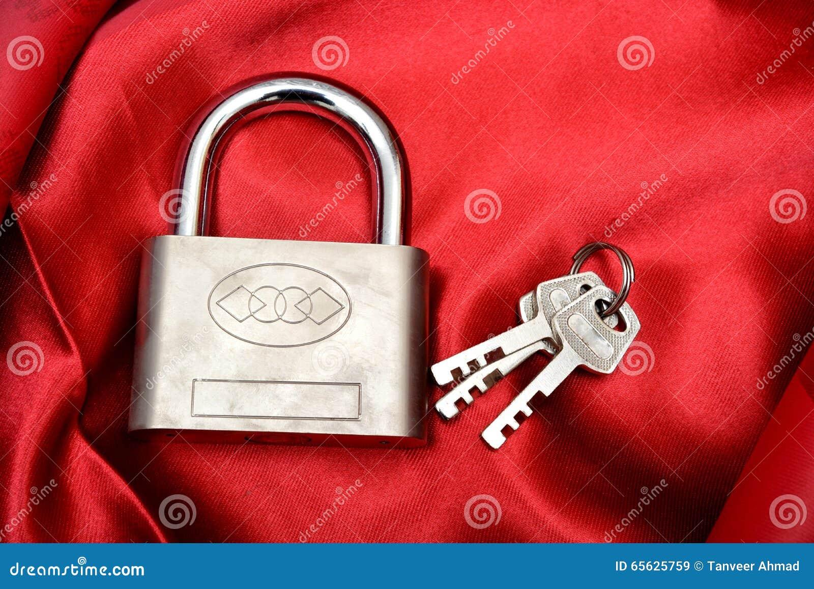 锁与在红色丝绸背景隔绝的钥匙