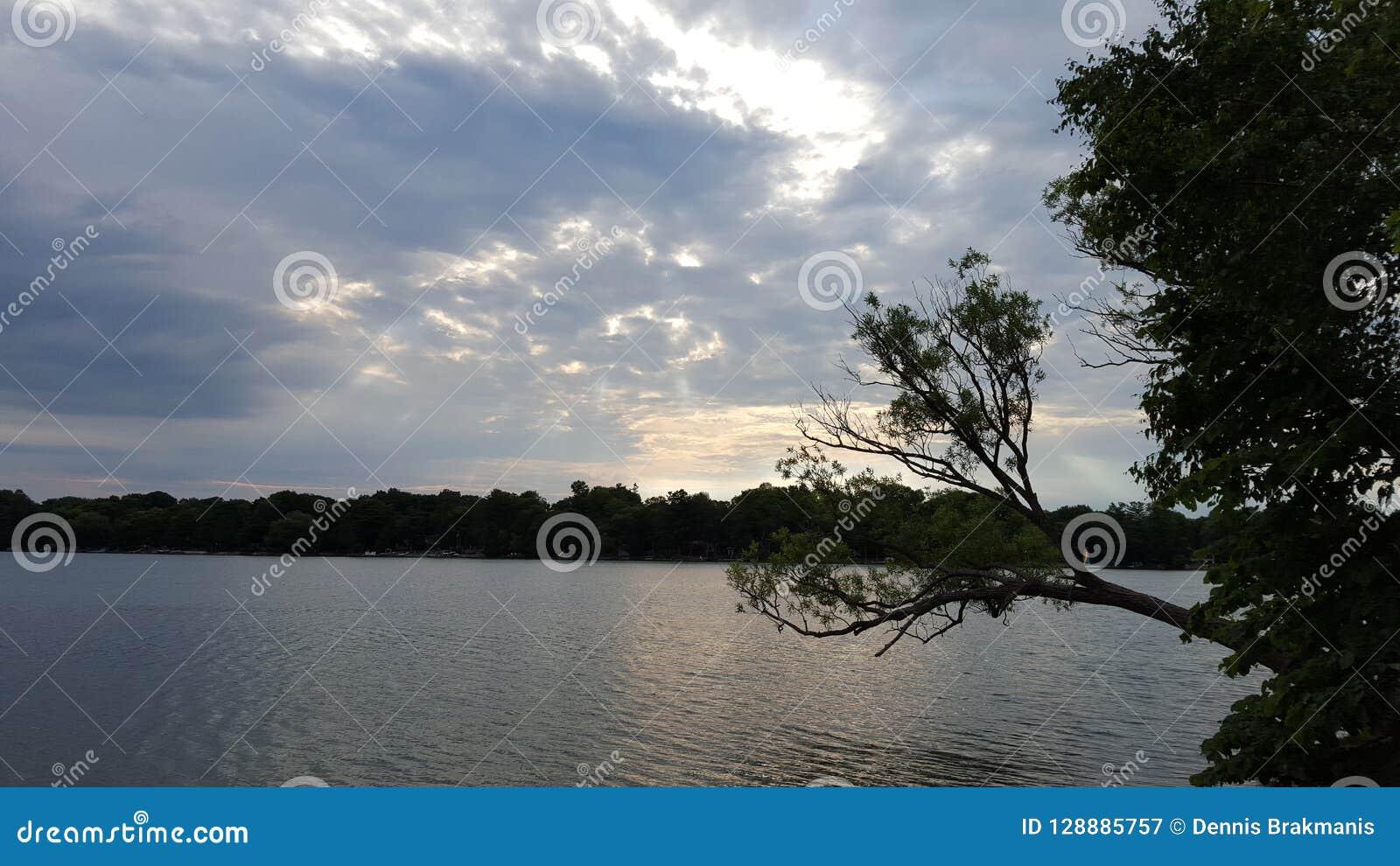 锐化在湖的阴暗多云天空外面的太阳