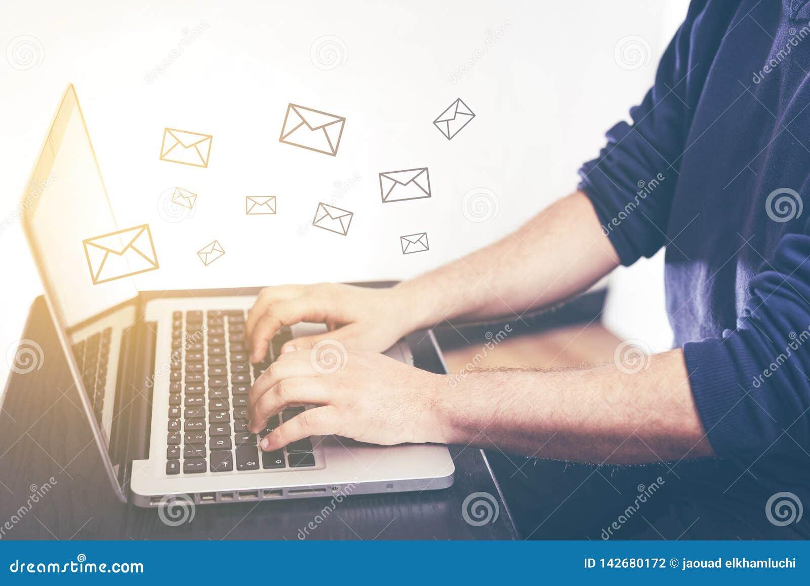 键入和送消息和膝上型计算机有电子邮件象电子邮件行销和时事通讯概念的人的手