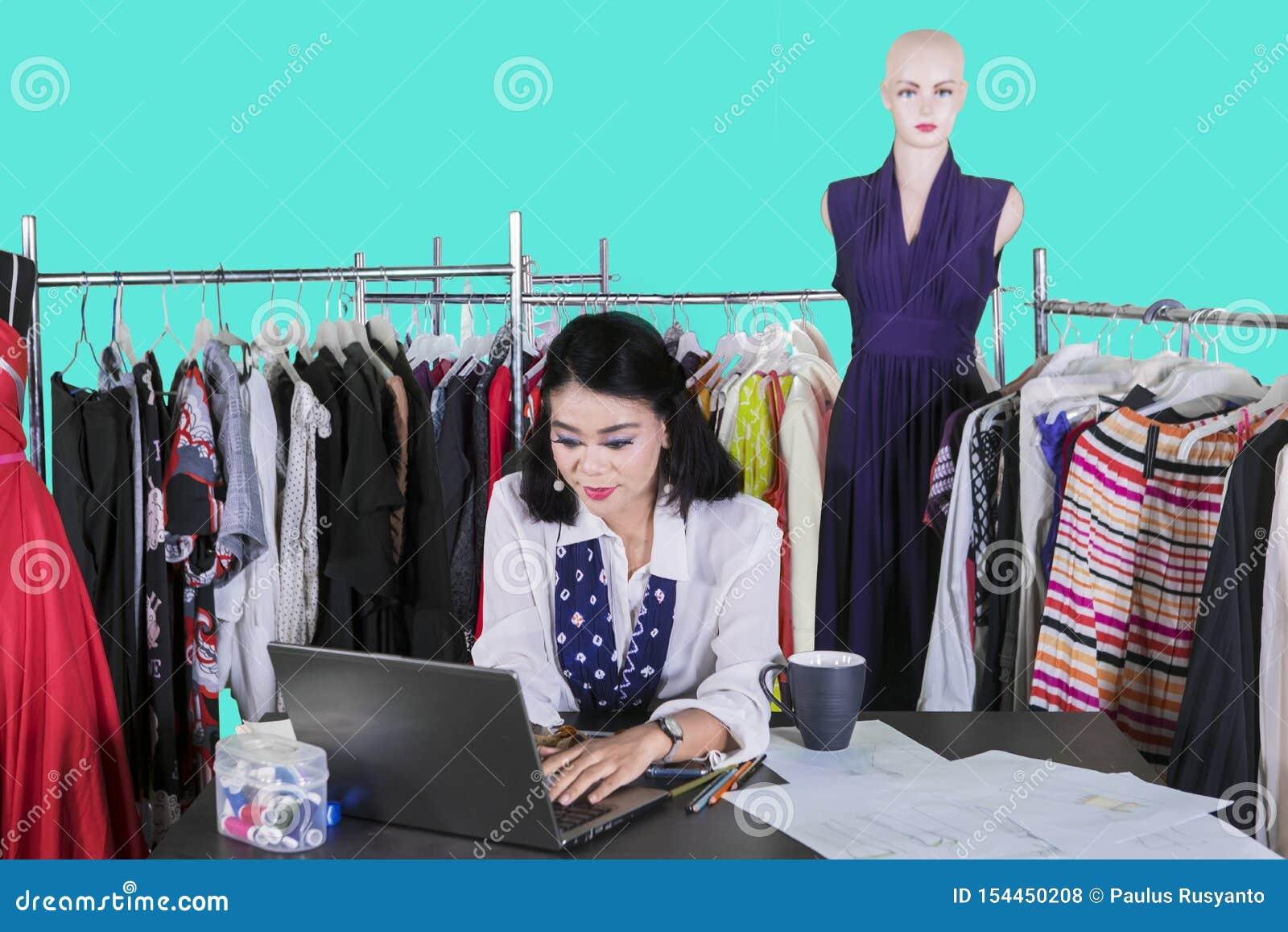 键入在膝上型计算机的女性时尚编辑