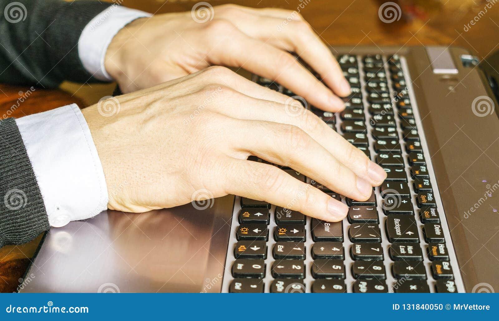 键入在膝上型计算机键盘特写镜头的手 背景生意人使用白色的计算机膝上型计算机