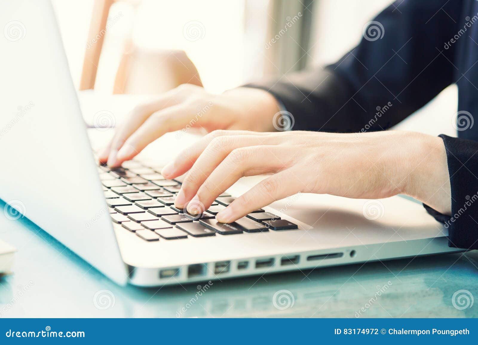 键入在键盘的女商人的女性手
