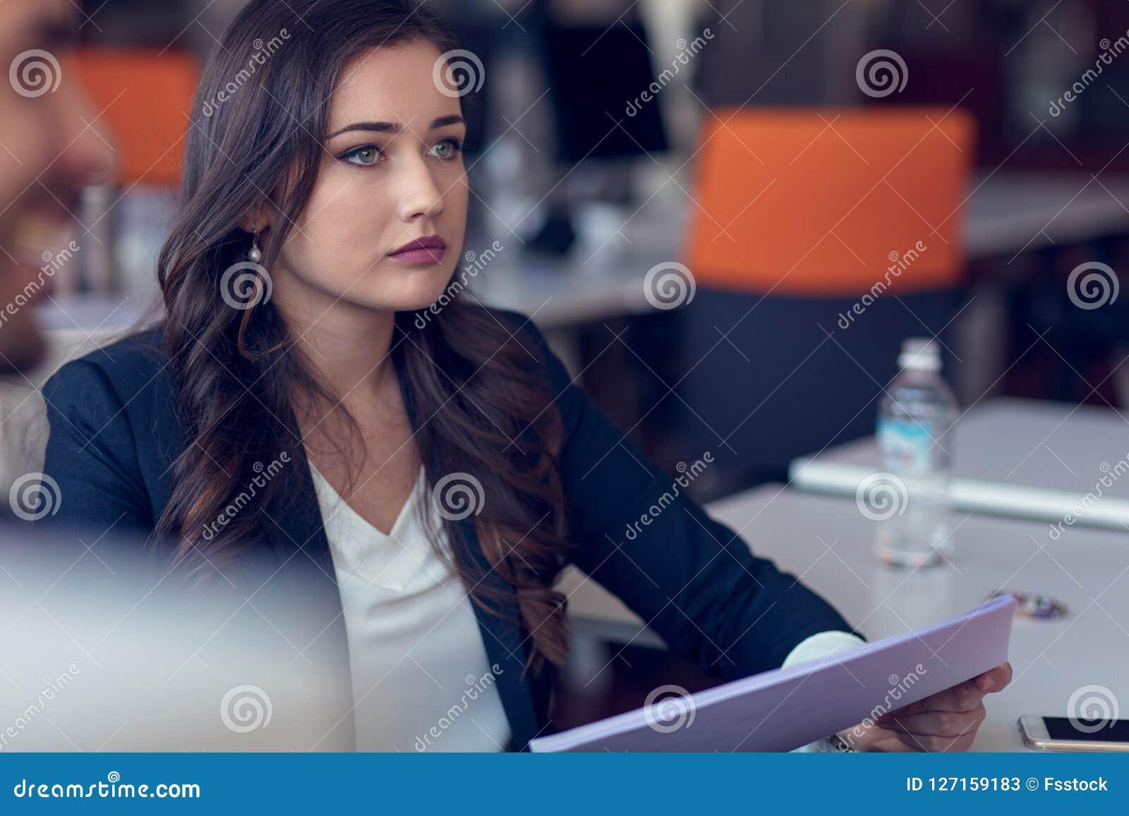 键入的企业消息 拿着巧妙的电话和看它与微笑的聪明的便衣的确信的少妇