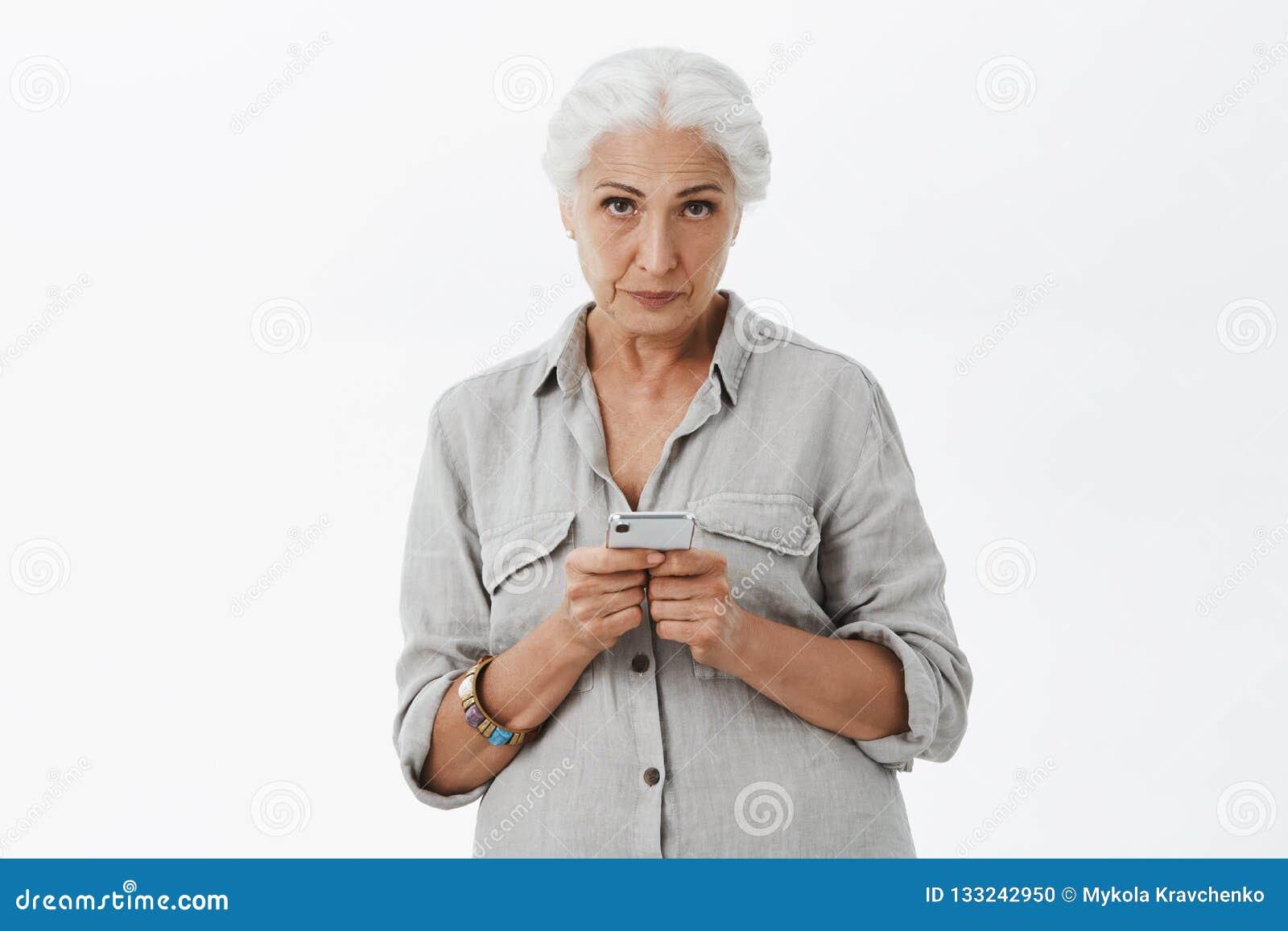 镇静和serious-looking被激怒的资深妇女室内射击有看与蔑视形式的灰色头发的在前额下