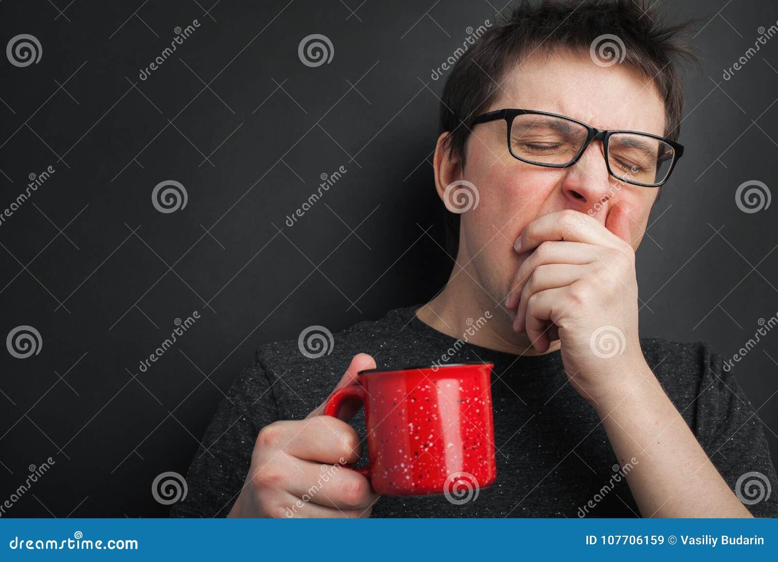 镜片的困打呵欠的人有红色茶的或咖啡有蓬乱的头发在黑背景,早晨的内衣刷新