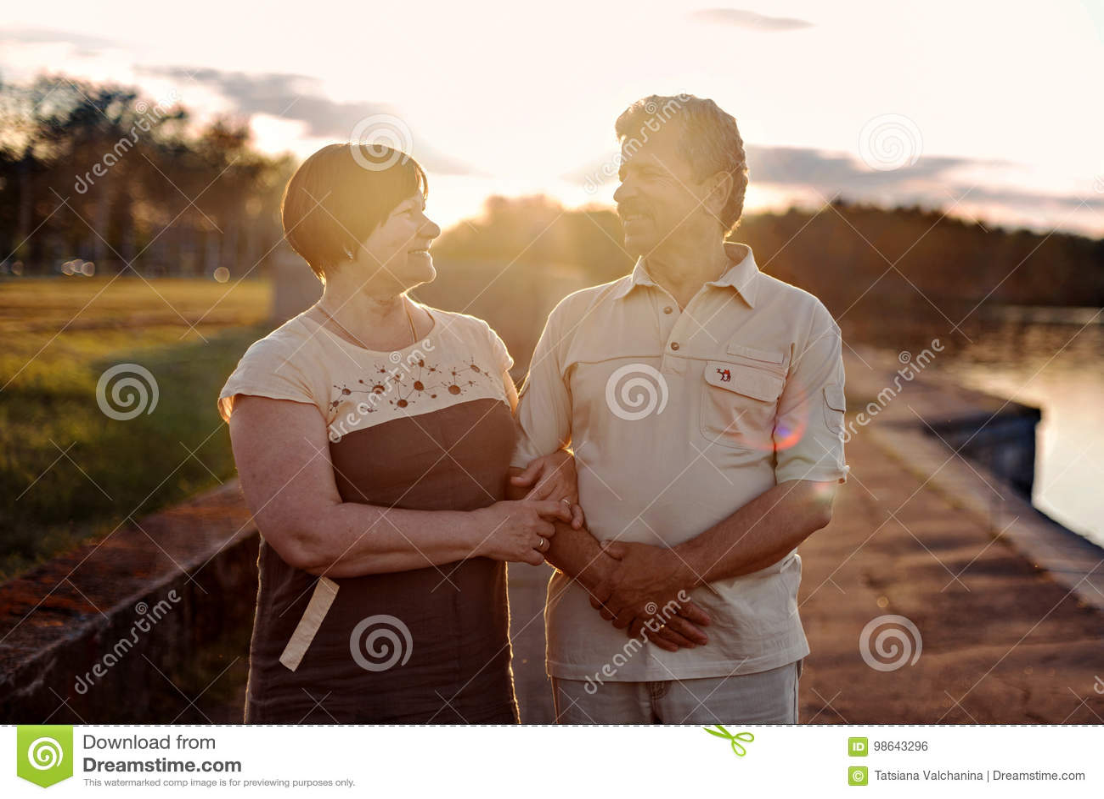 年长夫妇走的谈话嘲笑日落在湖河附近