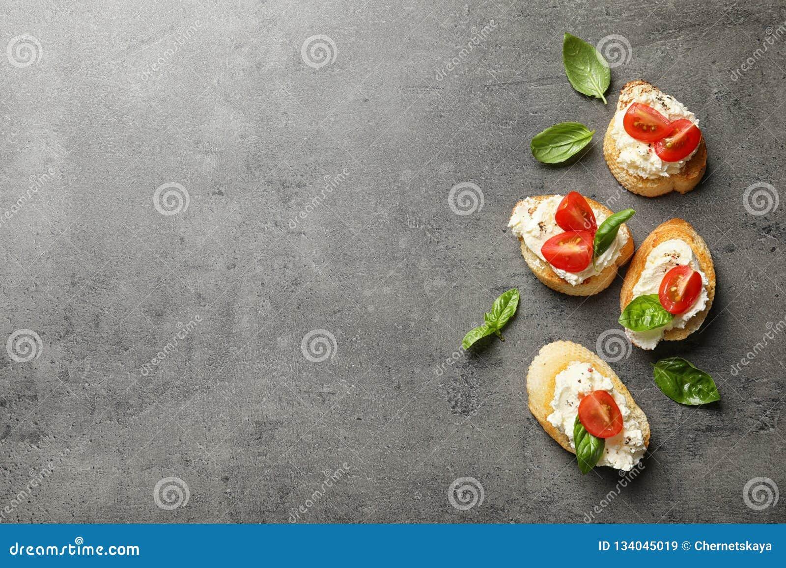 长方形宝石片断与鲜美奶油奶酪和蕃茄的在灰色桌,平的位置上
