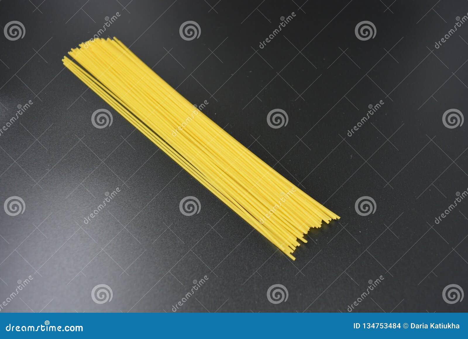 长的干细面条,从硬质小麦品种的意大利面团意粉在有趣的黑背景的组装