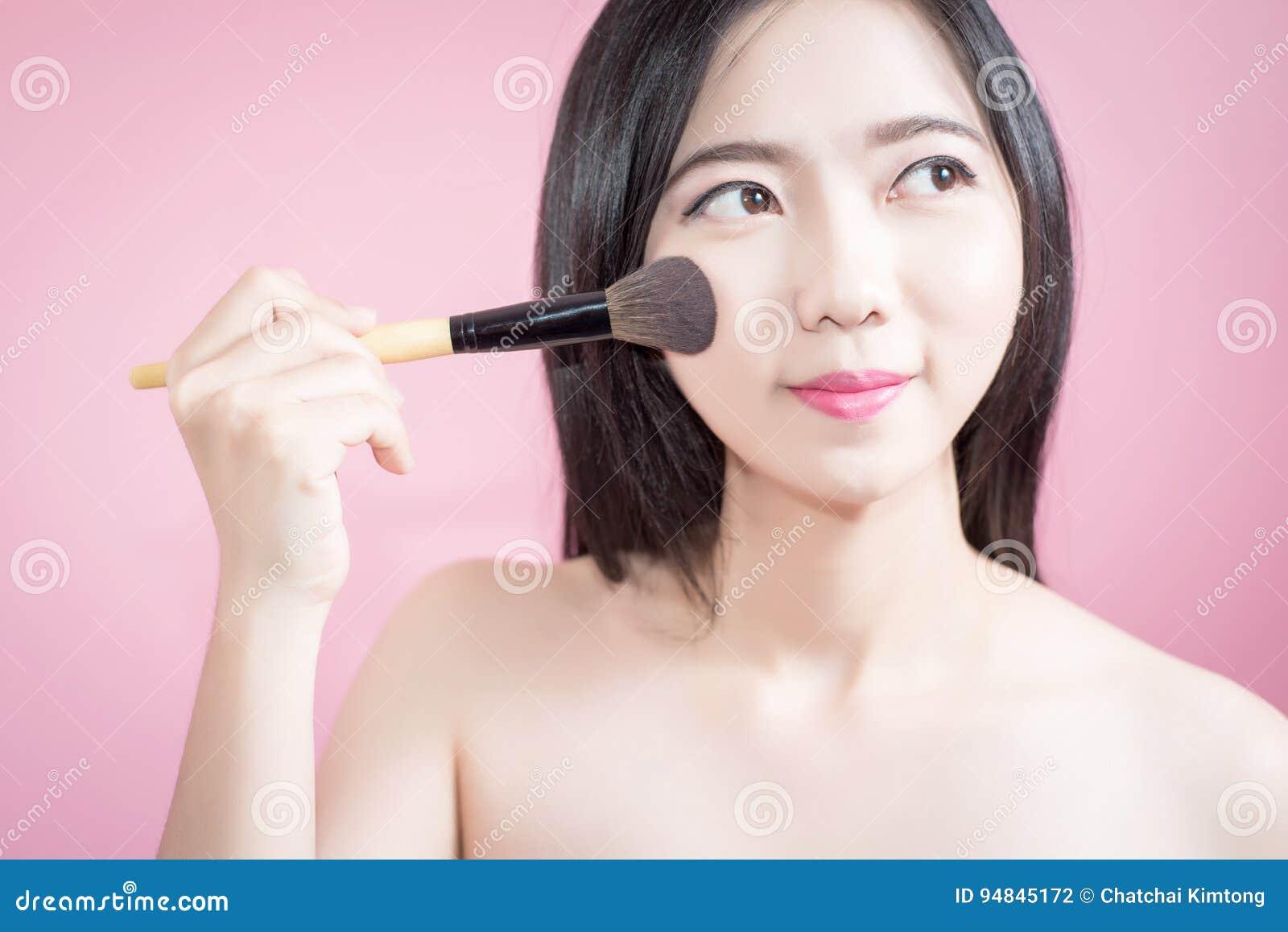 长的应用在光滑的面孔的头发亚裔年轻美丽的妇女化妆粉末刷子被隔绝在桃红色背景 自然的构成