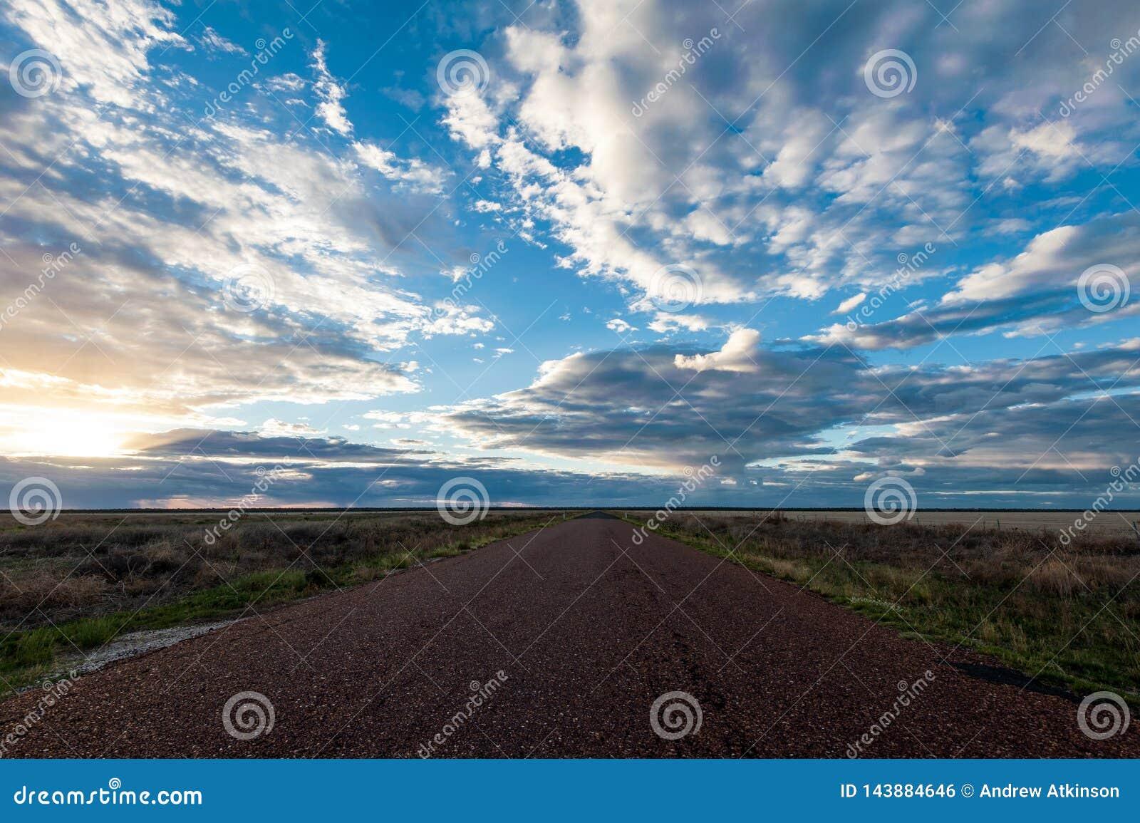 长的直路充分消失入遥远的天际在日落天空下云彩在澳洲内地