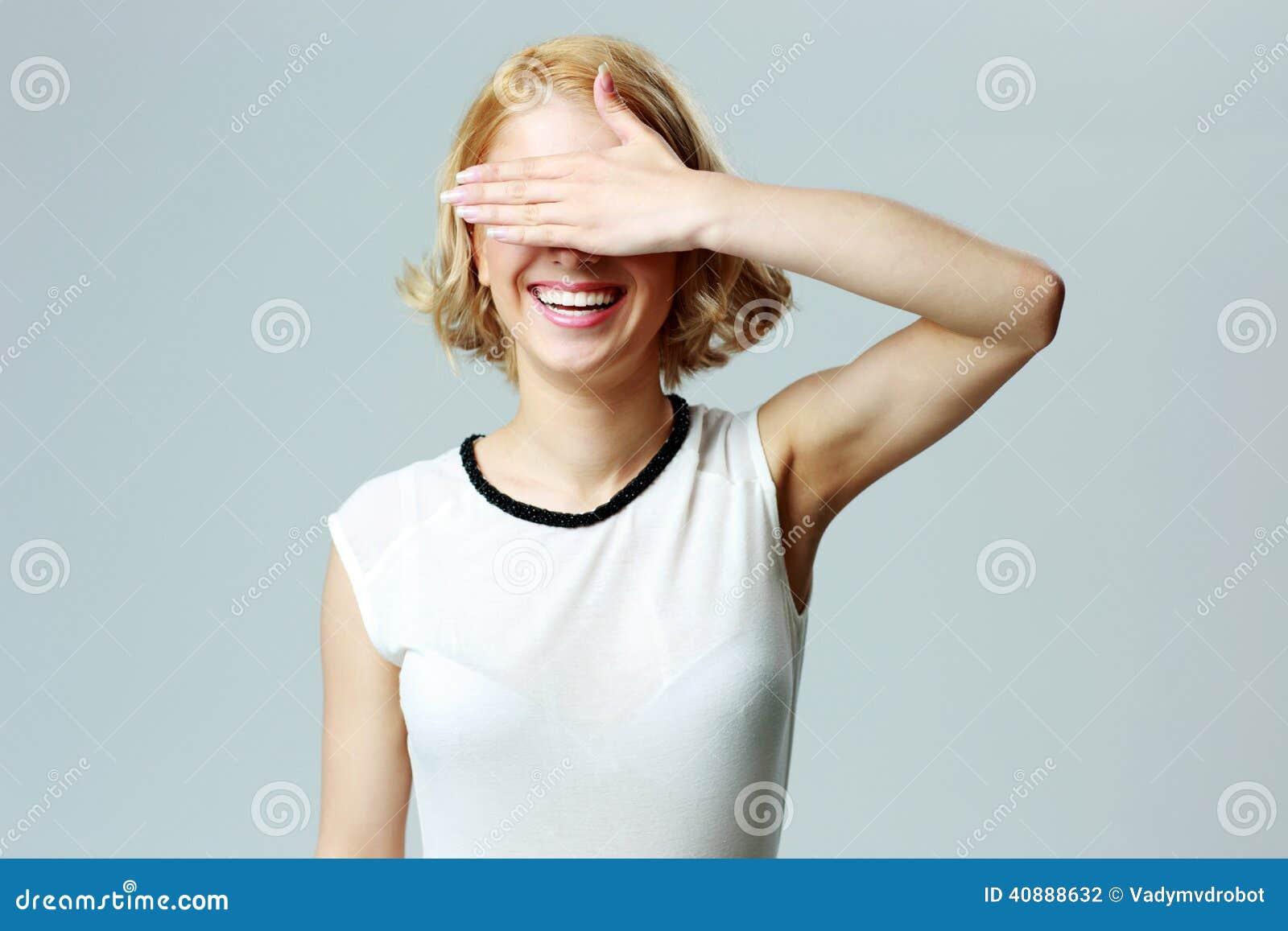 闭上�9�/9/h9�9��o^�_闭上她的眼睛与的一名笑的妇女的画象移交灰色背景.