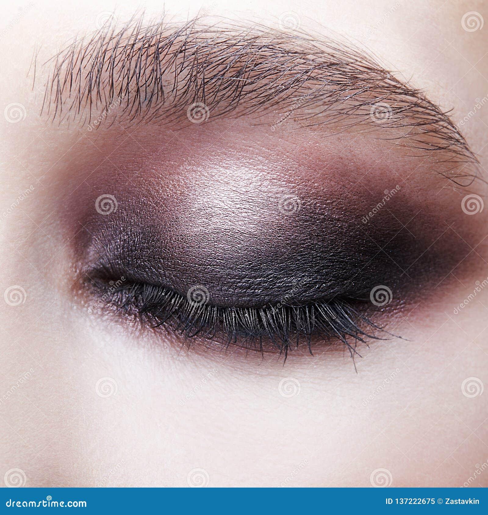 闭合的人的女性眼睛特写镜头宏观画象  有完善的紫罗兰的-黑发烟性眼睛构成女孩
