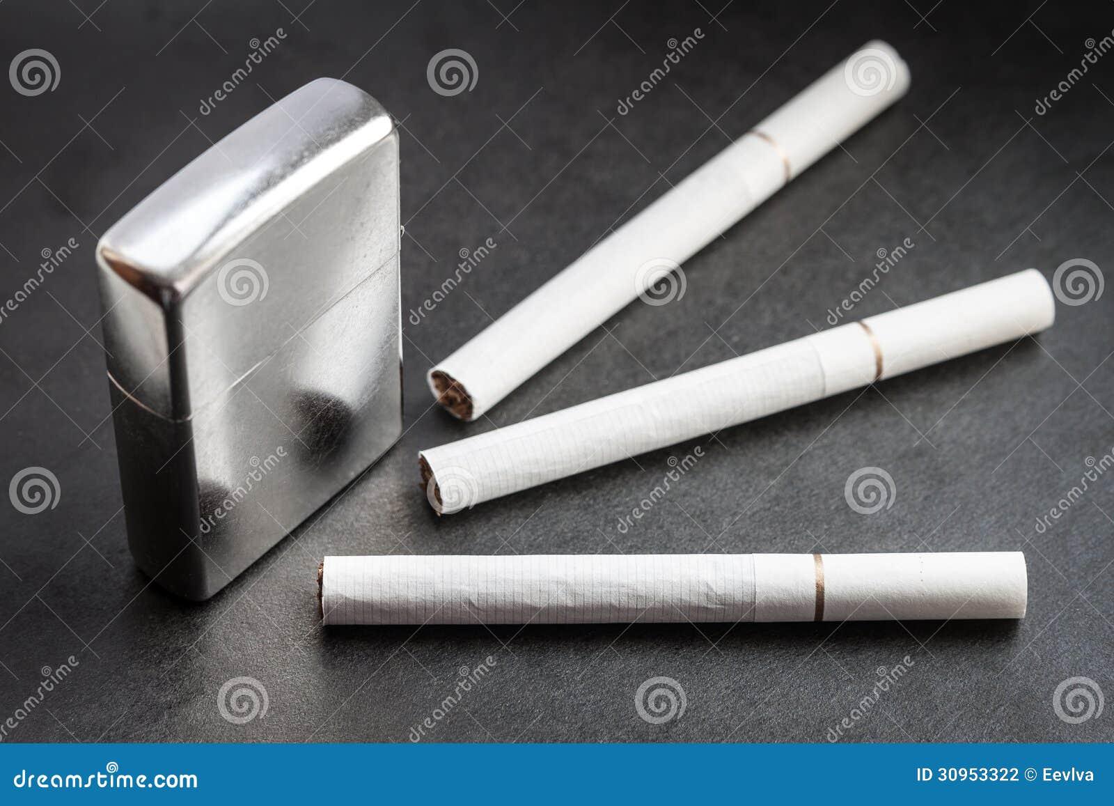 着打火机和烟的头像_闭合的金属打火机和三根香烟在黑暗的背景.在香烟的选择聚焦.